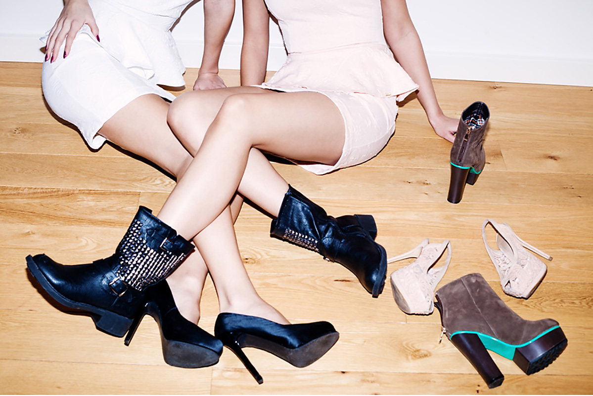 couple of girls with lots of shoes on the floor